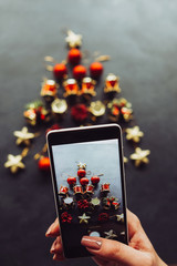 Hand holding mobile phone to make a photo of Christmas tree decoration. Blogger posting images to the social media concept