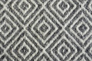 Woolen fabric texture close-up. Gray contrast diamond pattern