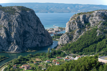 View to Omis from the mountains with the river Cetina, the town, the adriatic sea and in the background the island of Brac with a clear blue sky.