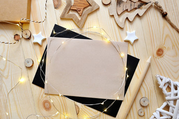 Christmas background kraft sheet of paper with place for your text and white christmas star and garland on wooden background. Flat lay, top view photo mockup