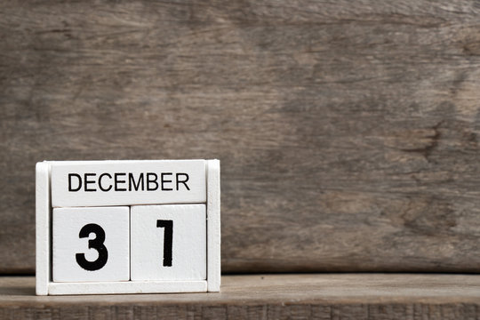 White block calendar present date 31 and month December on wood background