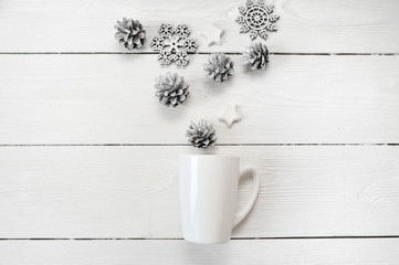 Mockup white mug with christmas cones and stars, on a white wooden background. Flat lay, top view photo mock up