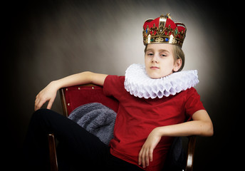 Crowned boy sitting in an armchair