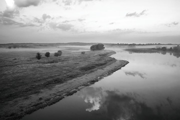 The sky at sunrise on the river, a misty morning, black and white photo