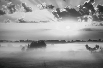 The sky at sunrise, dense fog on the meadow in early morning, black and white photo