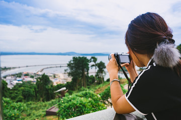 Female taking photo of seascape from view point.