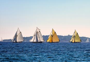 Four old sailboats on sea