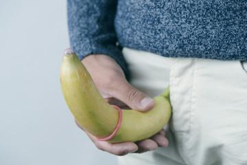 man holding a banana with a condom