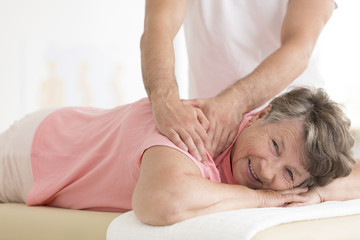 Masseur setting elderly woman shoulder