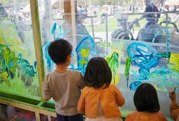 壁に絵の具で絵を描く子供たち