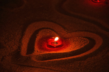 Red candle burning in heart shaped sand close up