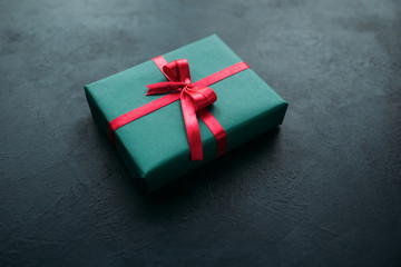 Christmas present in a red gift box on grey background. Festive season concept