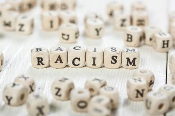 Racism word written on wood block.