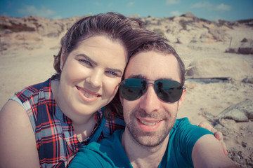Young couple taking selfie with smartphone or camera at the beach