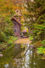 Old wooden water mill in the forest with reflect on water at autumn