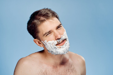 Man with a beard on a blue background in shaving foam, emotions, portrait