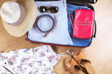 Open suitcase with casual female clothes hat, sunglasses, dress, shoes, on wooden floor top view close up. Packing travel bag for trip concept