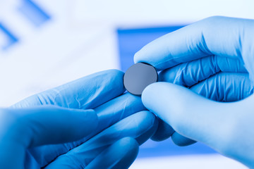 Scientist hold in hands in protective gloves small round piece of glass, new type of glass or plastic with new properties research concept