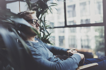 Attractive young man wearing glasses casual clothes.Man sitting in vintage armchair modern loft studio and relaxing whith headphone music. Blurred background.Horizontal.