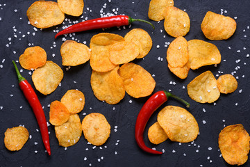 Potato chips with chili pepper flavour and salt on dark stone table surface flat lay top view
