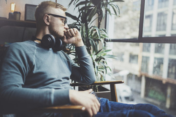 Pensive young man wearing glasses casual clothes.Man sitting in vintage armchair modern loft studio and relaxing whith headphone music.Panoramic windows on blurred background.Horizontal.
