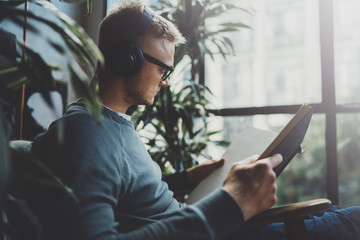 Attractive young man wearing glasses casual clothes.Man sitting in vintage armchair modern loft studio, reading book and relaxing whith headphone music. Blurred background.Horizontal.