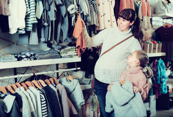 Pregnant mother and girl child choosing clothes