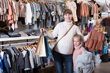 Positive pregnant mother and girl enjoying purchases