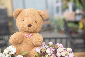 Teddy bear on a flower background blurred