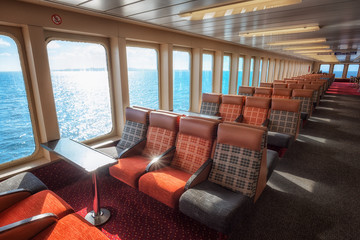 Interior of a ship with empty passengers seats and sea view.