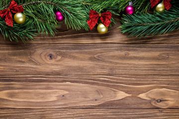 Nice christmas theme on the wooden background with pine tree branches on the top of the screen