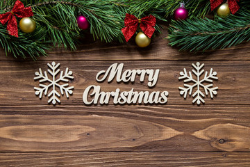 Merry Christmas on the center of the wooden background with pine tree branches on the top of the screen and two beautiful snowflakes