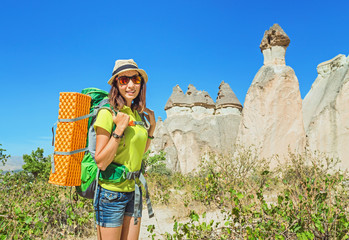 Young happy woman traveler alone hiking with backpack in the Pasabag valley of Cappadocia, Turkey