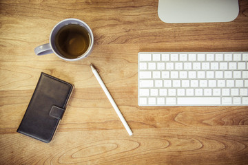 Wood office desk with keyboard, cup of tea, phone, pencil