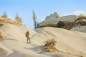 Group of Friends with backpack travelling among Cappadocia fairy chimneys at summer, concept of tourism in middle east