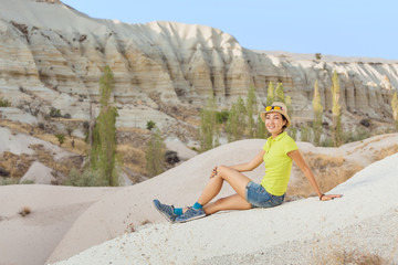 Young happy woman traveler hiking with backpack in the love valley of Cappadocia, Turkey