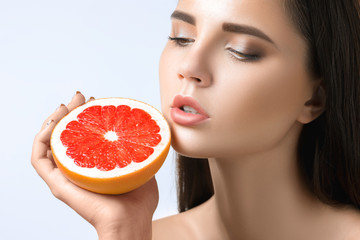 Pretty woman with delicious grapefruit in her arms.