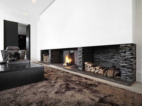 Modern livingroom with large fireplace with black furniture
