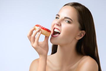 beautiful woman biting a donut