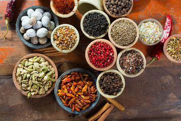 Variety of different asian and middle east spices, colorful assortment, on old wooden table