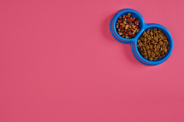 Dry pet food in bowl on pink background top view
