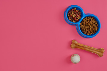 Dry pet food in bowl with a ball and dog bone on pink background top view