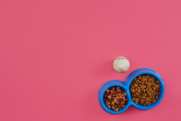 Dry pet food in bowl with a ball on pink background top view