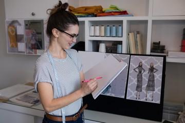 Female fashion designer drawing sketch on paper