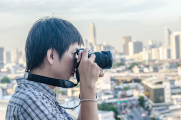 Thai photographer or traveller using a professional mirrorless camera in the cityscape for background