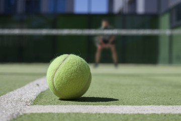 Tennis ball on a tennis court with tennisplayer out of focus.