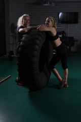 Fitness women are posing near a tire in the gym.