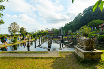 Fototapete - Stone sitting bull and main pond with stone causeway and fountains at Tirtagangga temple garden, in Bali, Indonesia