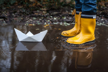 Child with Yellow Rain Boots and a little White Paper boat / Ship: Playing in a puddle, dreaming about his adventures