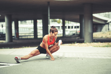 Female runner stretching and relaxing on  city street after jogging.
